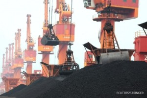 FILE PHOTO: Imported coal is seen lifted by cranes from a coal cargo ship at a port in Lianyungang, Jiangsu