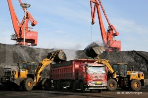 FILE PHOTO: Front loaders transport coal to a truck at a port in Lianyungang, Jiangsu province, China December 8, 2018. REUTERS/Stringer/File Photo ATTENTION EDITORS - THIS IMAGE WAS PROVIDED BY A THIRD PARTY. CHINA OUT.