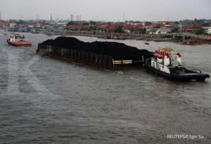 FILE PHOTO: A coal barge passes along Musi river in Palembang